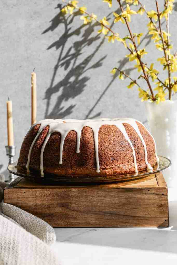 a gluten free hummingbird bundt cake with glaze on top sitting on an antique yellow plate and a wooden box