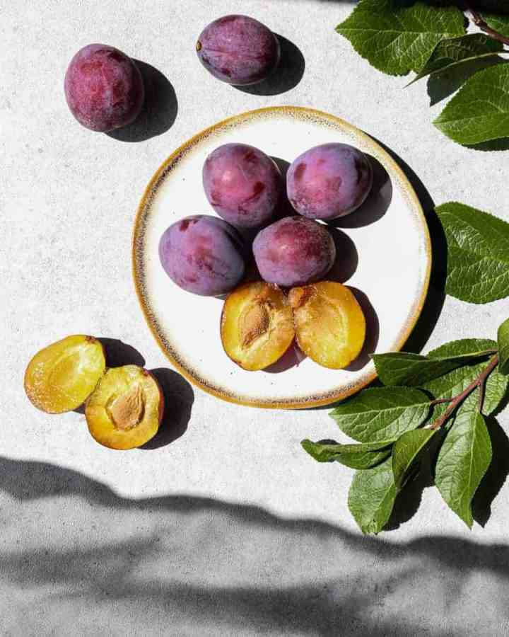 some of my favorite things 0 fresh purple plums with a yellow center on a plate with a plum tree branch laying beside it