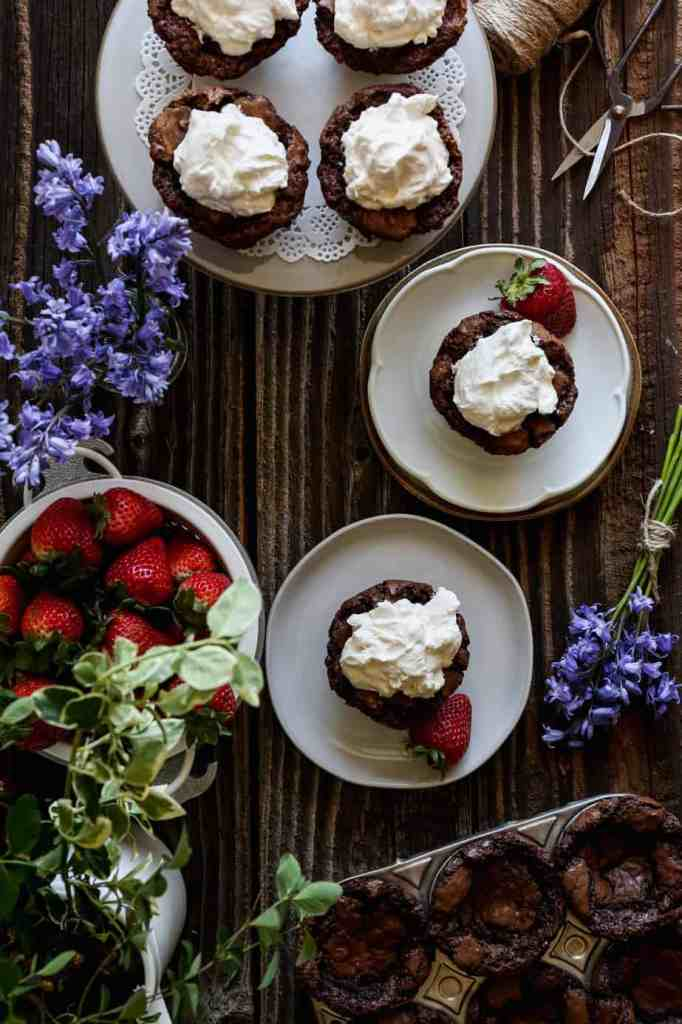 a plate and a cake stand with gluten free brownie bites topped in homemade whipped cream with fresh strawberries