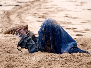 Child digging hole in the sand at the beach