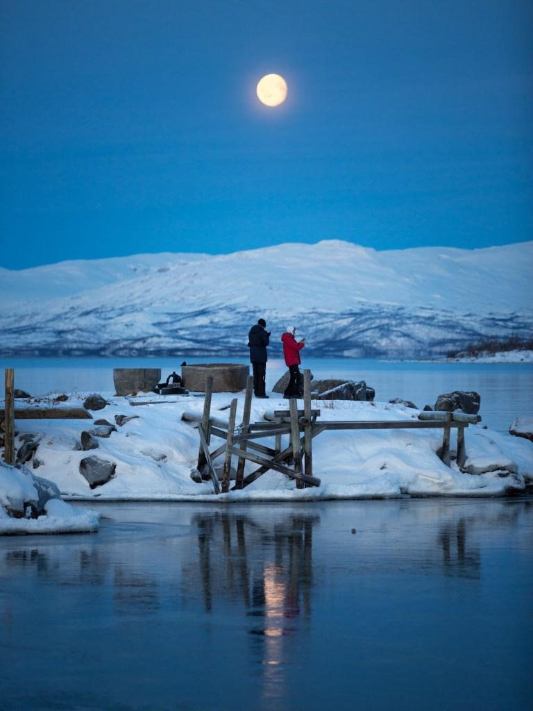 Luna piena a mezzogiorno sul lago Torneträsk durante notte polare