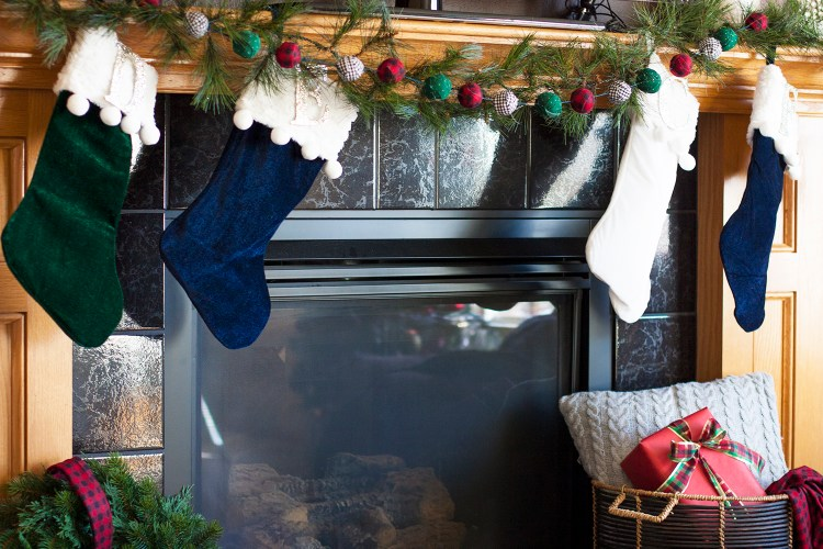 A beautiful Christmas fireplace mantel. Those velvet stockings have the cutest pom poms! And that DIY garland is so cute! christmas home tour | holiday homes | christmas house | christmas tree pictures | christmas mantel | christmas living room | christmas blog home tour