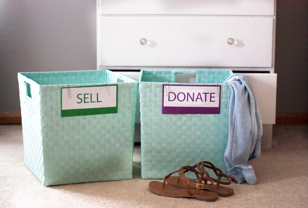 aqua-bins-with-sell-and-donate-signs-on-them-in-front-of-white-dresser