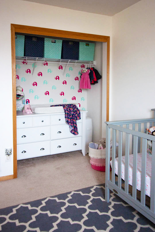 colorful-nursery-with-temporary-wallpaper-behind-white-changing-table-in-closet