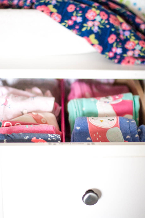 folded baby clothes in a nursery dresser
