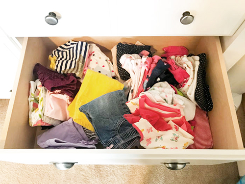 Messy, unorganized baby clothes in a dresser drawer
