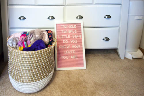 pink-letter-board-propped-against-white-dresser-in-a-nursery