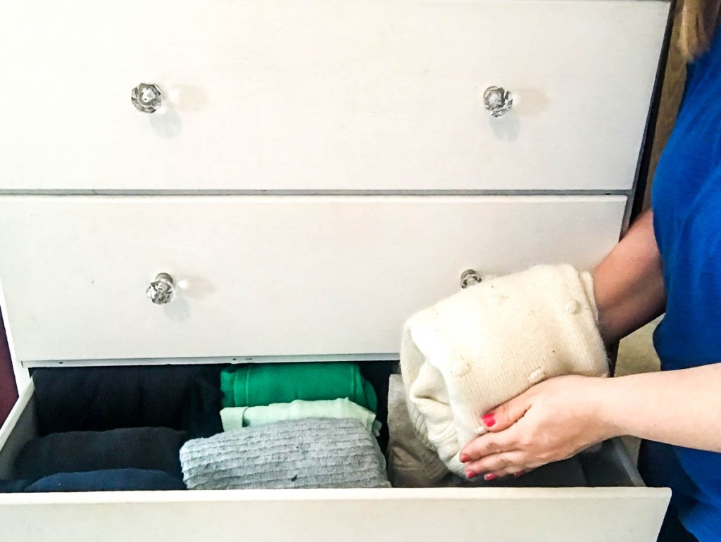 girl-folding-sweater-next-to-organized-dresser-drawer