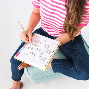 top down look at girl writing inside Powersheets Goal Planner