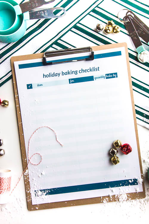 holiday baking printables on clipboard with christmas props on