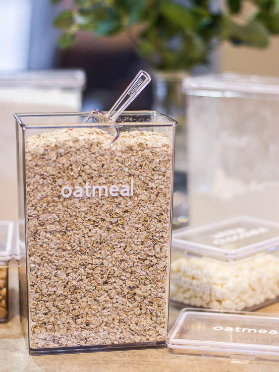 "clear canister with oatmeal and a white vinyl ""oatmeal"" label"