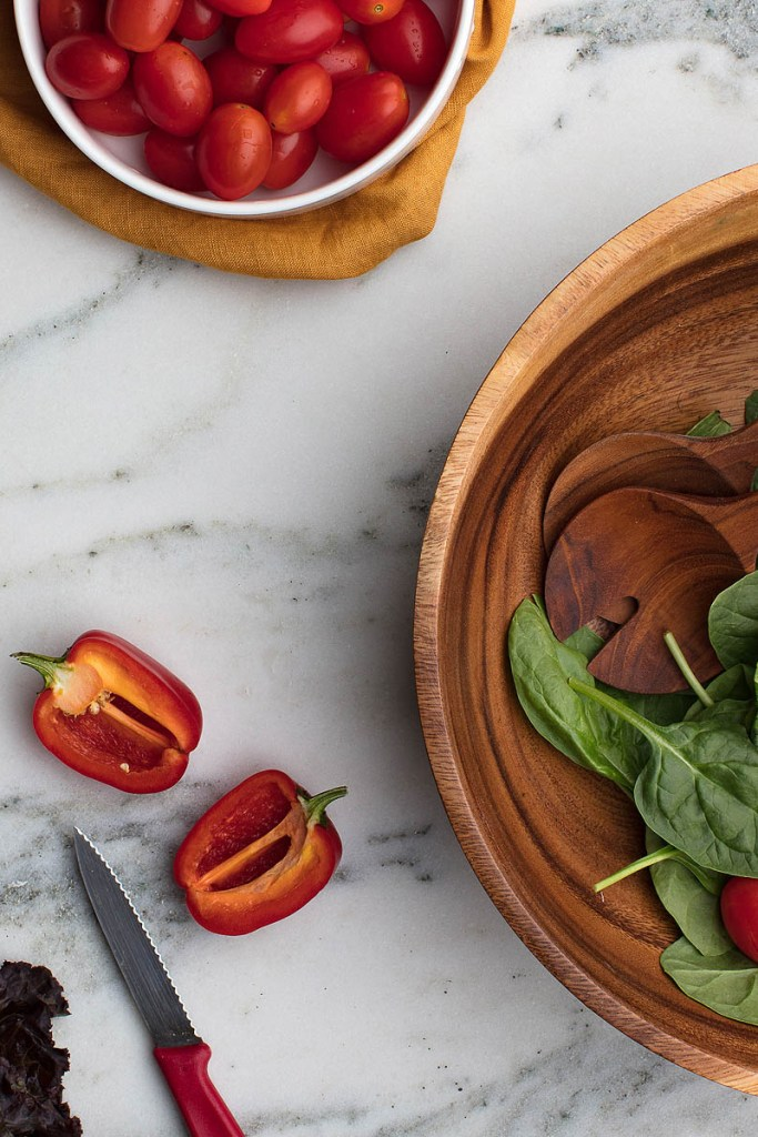 wooden bowls with salad on marble counter