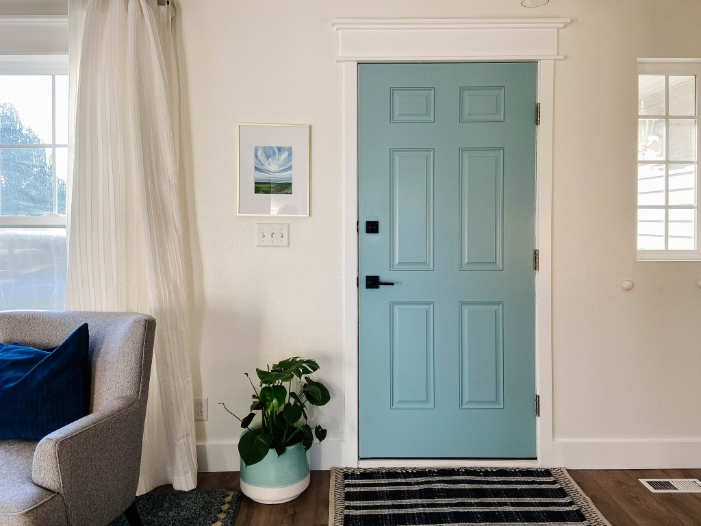 interior front door with blue paint, dark modern hardware, and black and white rug