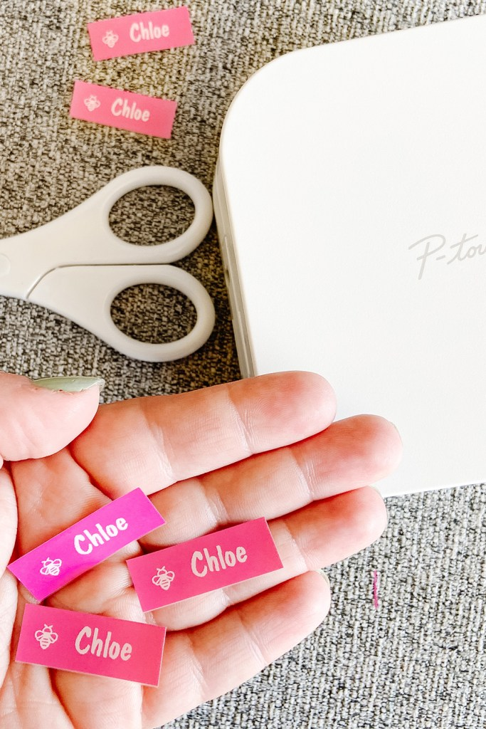 hand holding pink labels with brother cube label maker