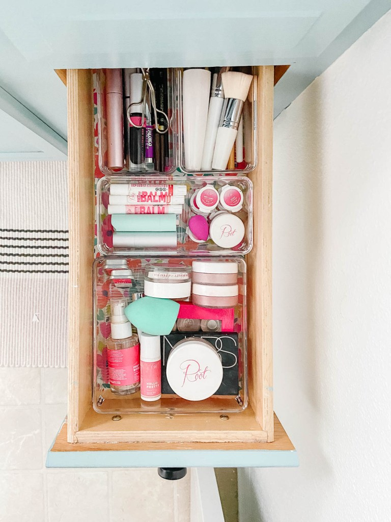 bathroom drawer with clear containers full of makeup