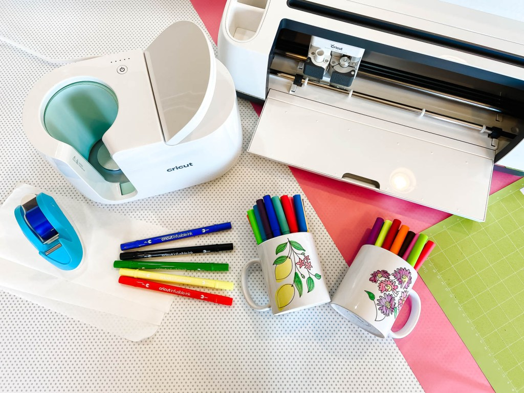 Cricut Mug Press, Cricut Maker, and supplies for DIY mugs on table