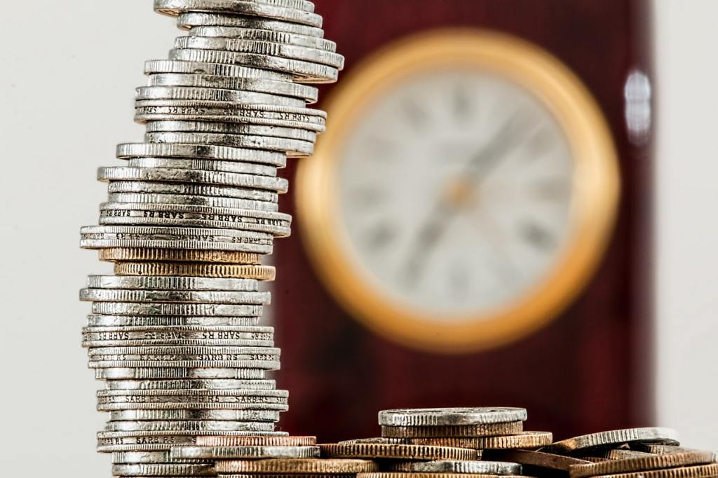 stack of coins showing growth with clock in background