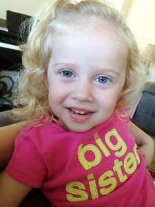 "toddler wearing a shirt that says ""big sister"""