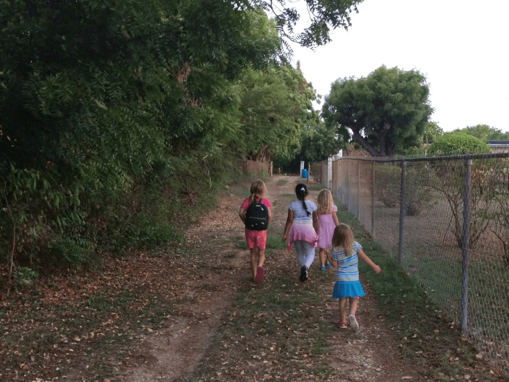 four girls walking down a lane