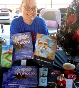michelle buvala sits at a table of books from teh apples for the princess series