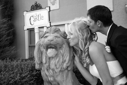 Happy couple kissing lion at cavender castle