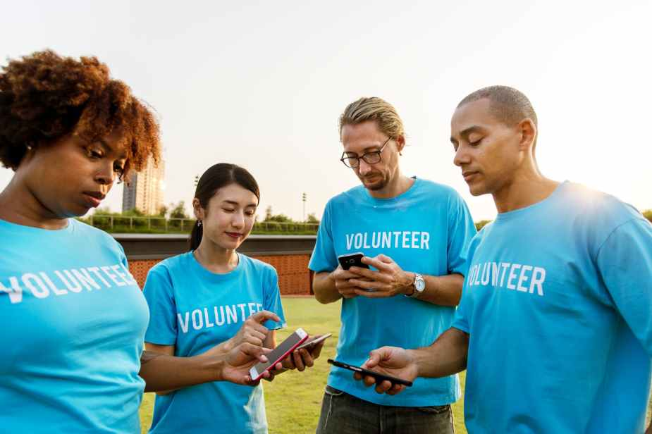 four person wearing blue volunteer crew neck t shirts