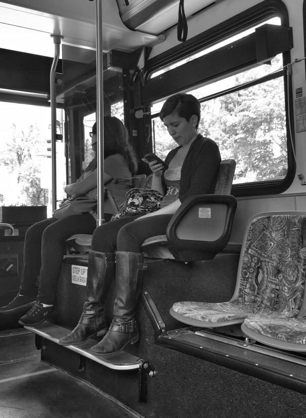 Woman checking her phone will ridingon A montgomery County Ride On bus