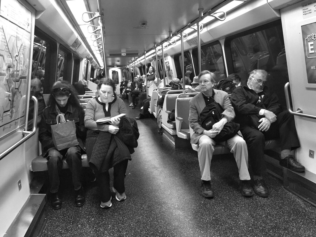 people seated two by two on a metro car in washington dc
