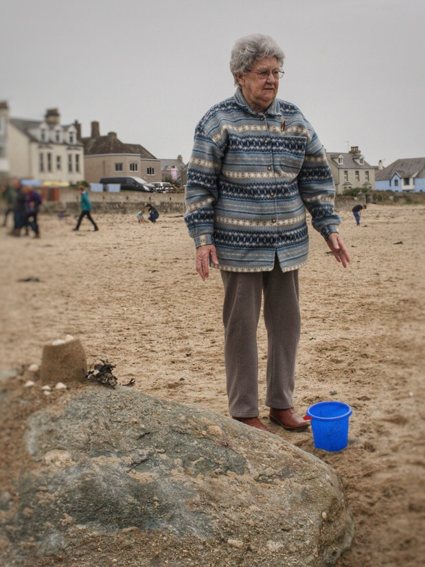 Great grand mother playing on the beach with one of her great grand children