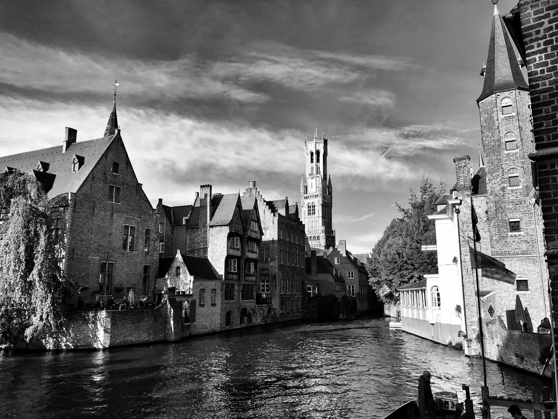 Enjoying the canal of Bruges, Belgium on a beautiful, sunny afternoon