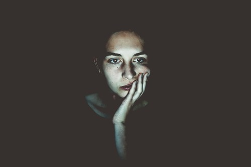 Woman in the dark with hand over her cheek - SmarketryBlog.com - Photo by Niklas Hamann/Unsplash