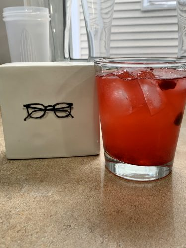 A cranberry mojito next to a pair of eyeglasses