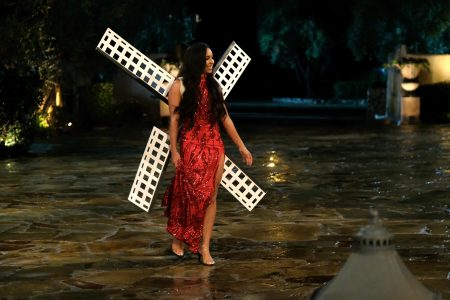 Deandra wears a red evening gown with windmill sails attached to the back