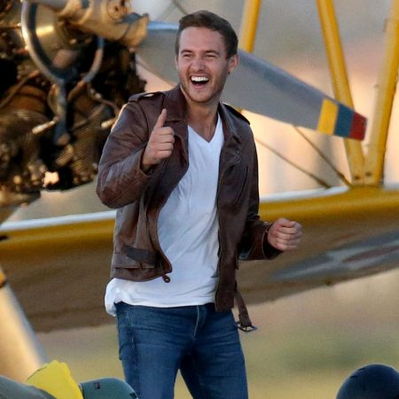 Peter wears an aviator jacket and gives a thumbs up in front of a plane.