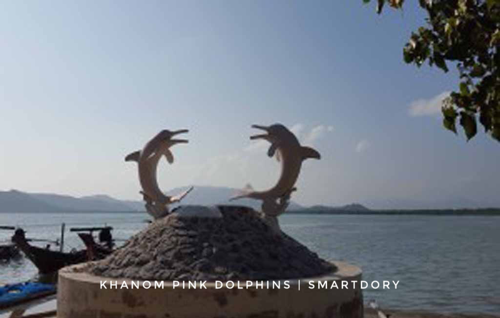 A statue of two pink dolphins.