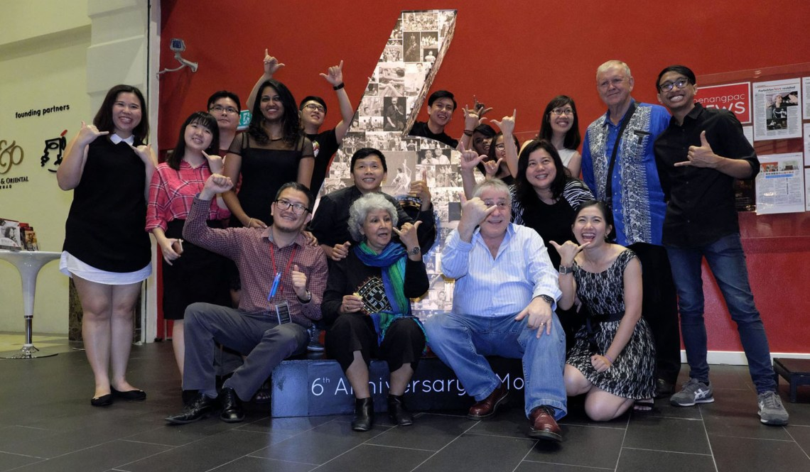 """A group photograph of 17 people around a light box with the number 6 on display. Identified in the photo are Dato' Faridah Merican, Joseph Christopher """"Joe"""" Hasham (OAM), Pauline Lye, Alexander Ooi and Martin Rutherford. Photograph is taken during penangpac 6th anniversary celebration at Straits Quay, Seri Tanjung Pinang, Penang on 15 June 2017"""