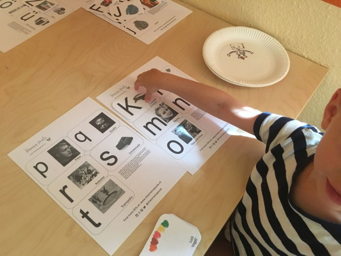 Wie lernen Kinder lesen? Kind spielt mit selbst gemachten Buchstaben Karten. Die Karten haben einmal Großbuchstaben und einmal Kleinbuchstaben. Die zueinander gehörenden Karten müssen vom Kind gefunden werden. Durch Motive, die dem Kind gefallen fällt das Lernen leichter. Dieses Spiel hilft beim Lernen der Groß- und Kleinbuchstaben und schließlich zum Lesen lernen.