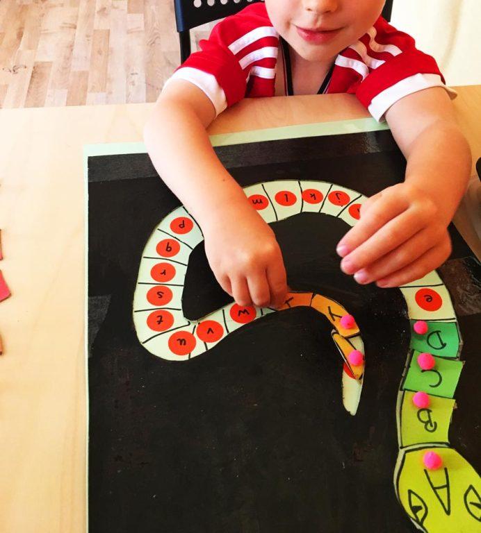 Selbstgebasteltes Buchstaben Puzzle Buchstaben Schlange Kind spielt mit Puzzle und legt die Großbuchstaben an die richtige Stelle