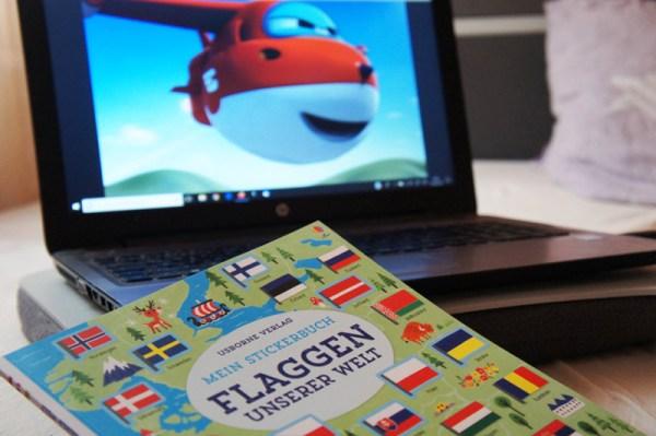 Lernspielzeug ab 6 Jahre Superwings auf dem Laptop im Hintergrund. Davor liegt das Stickerbuch Flaggen unserer Welt