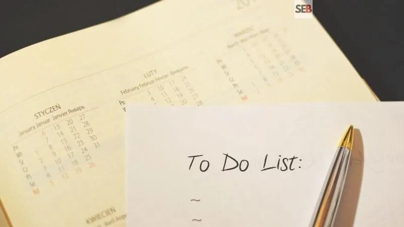 Event planning checklist - pen and paper written to do list on top a calandar