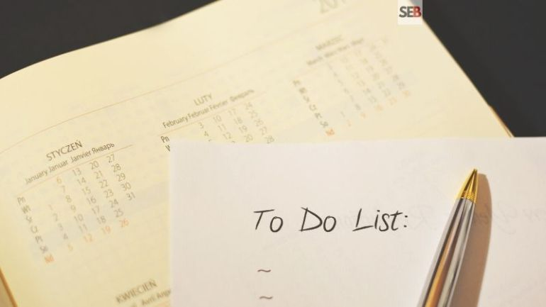 Event planning checklist - pen and paper written to do list on top a calandar