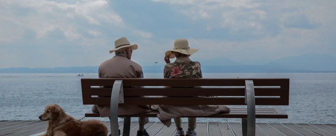 Older Couple Sitting On Park Bench