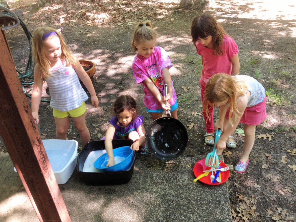 Daisy Girl Scouts washing dishes at camp