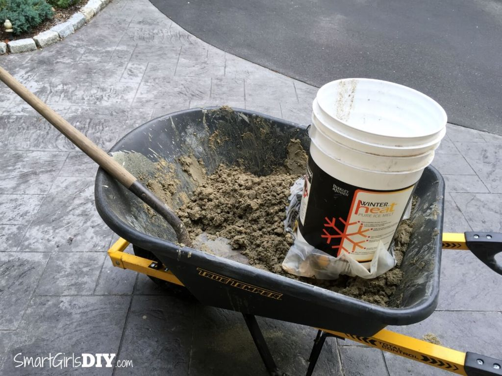 Mixing deck mud in a wheel barrow for a DIY shower pan