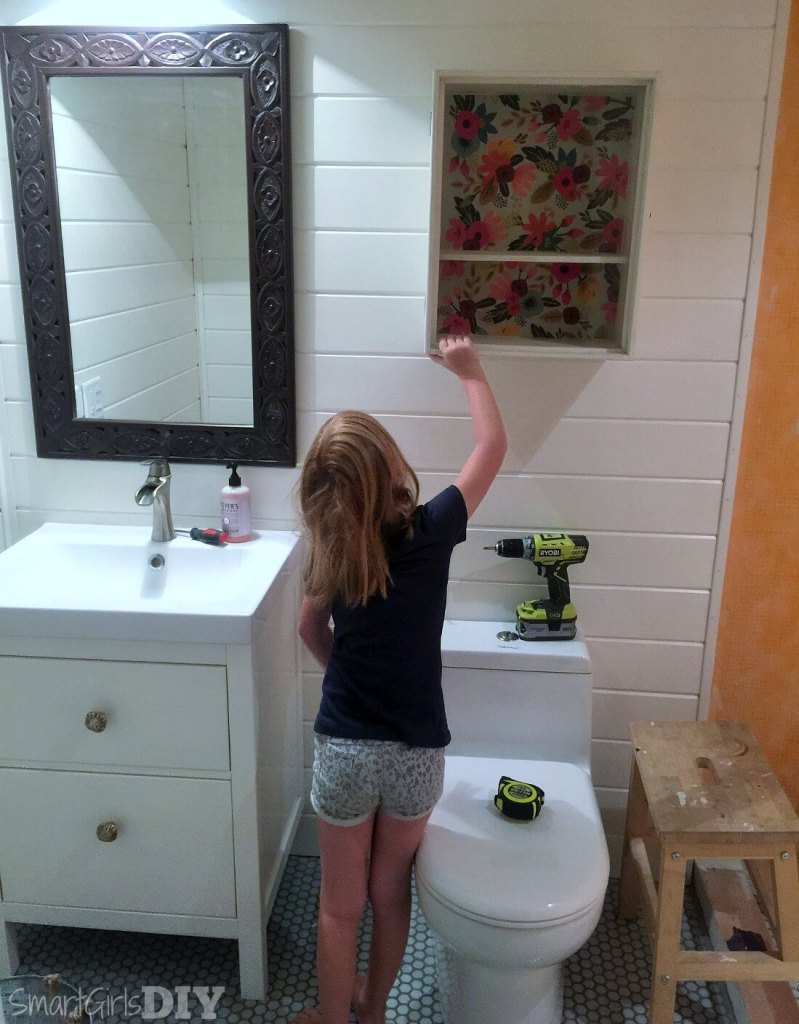 Mommy's little helper holds up a wall cabinet