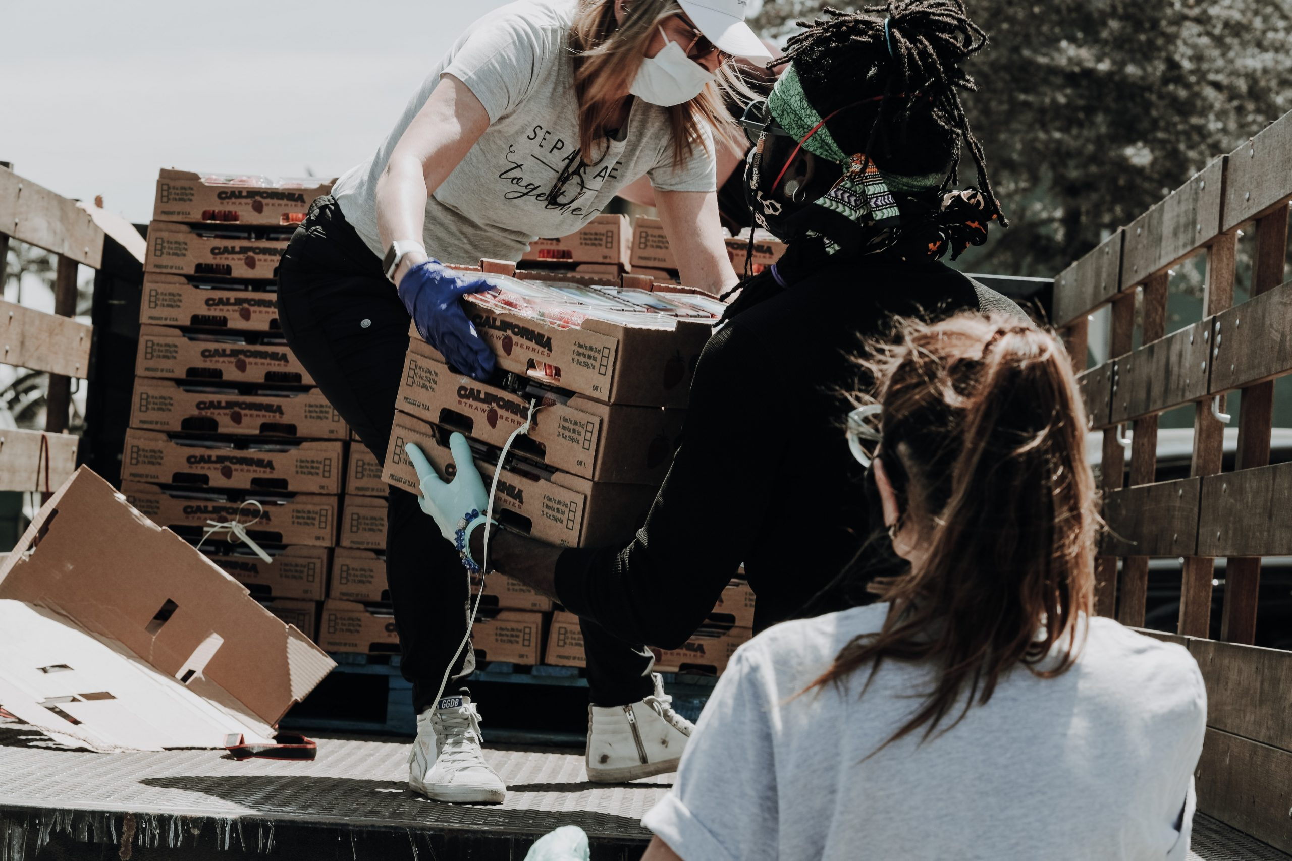 Three volunteers wearing face masks unload crates of strawberries off of a truck