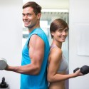Fit couple lifting dumbbells together smiling at camera at the g