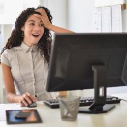 Mixed race businesswoman gasping at computer at desk in office