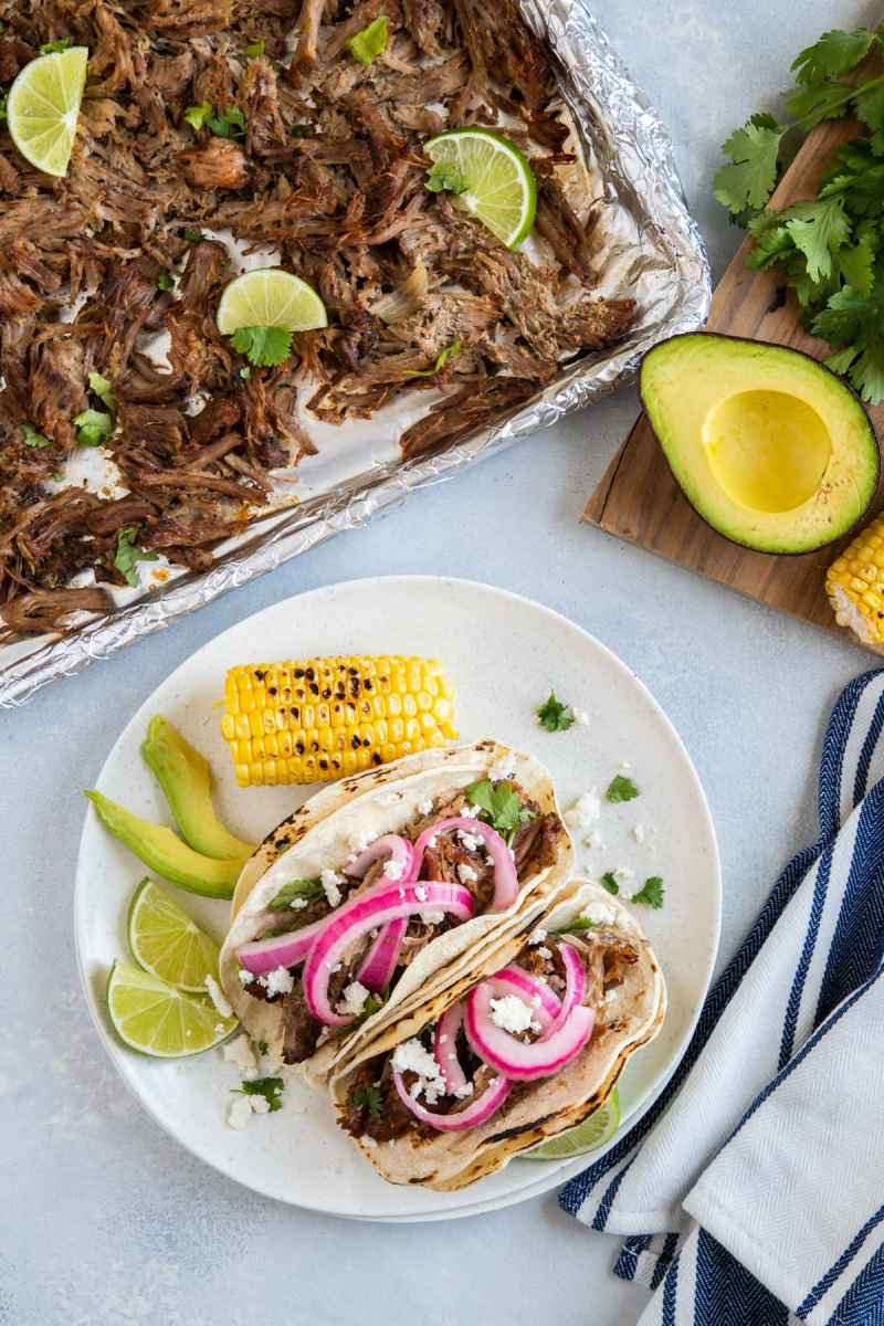 Pork Carnitas on a baking sheet and a plate with two served carnitas tacos topped with pickled onions, avocado and corn.