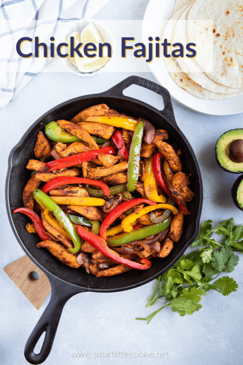 Chicken Fajitas in a skillet with flour tortillas, avocado, cilantro and lime wedges on the side.
